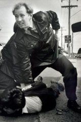 Constable Glenn Pullin arrests a man outside the rollerskating rink in Noble Park in 1992.