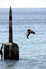 Boys jump off the pylon at Cottesloe beach.