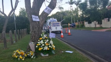 Floral tributes for Dr Zeng in Delfin Drive on Wednesday His home has a yellow fence and a blue SUV in the driveway.