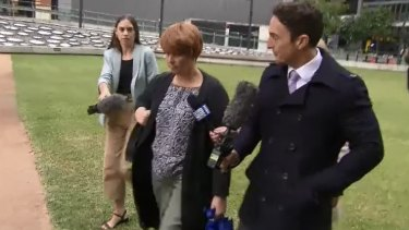 Julene Thorburn leaves a Brisbane court in disguise on Tuesday, donning a fake red wig and a change of clothes after testifying to the Tiahleigh Palmer coronial inquest.