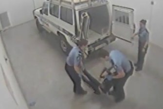 Footage of Ms Dhu being loaded into the back of a police van.