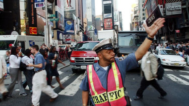 A New York City police officer directs traffic through New York's Times Square.