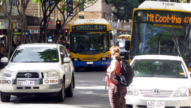 Buses, cars and pedestrians jostle for position on Adelaide Street in Brisbane's CBD.