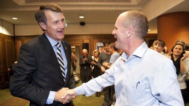 Cr Quirk shakes hands with his mayoral predecessor, Campbell Newman.