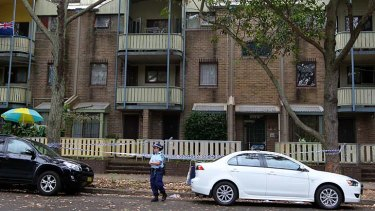 Police at a unit block on Walker Street, Waterloo, after Mr Scarman's body was found.