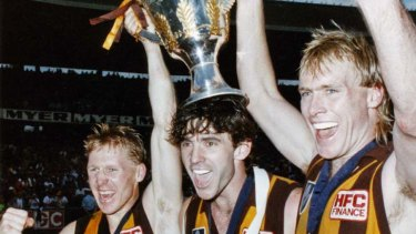 Hawks Andy Collins, Dean Anderson and Peter Curran celebrate with the 1989 premiership cup.