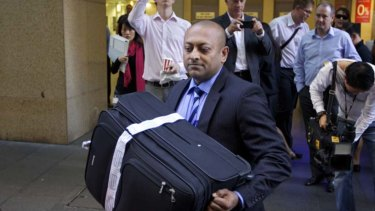 Detective Sergeant Ron Prasad with the suitcase seized from Michael Williamson during a 2012 raid on the HSU's Sydney offices.