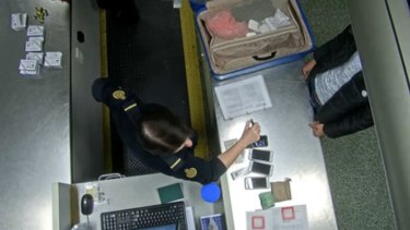 Mobile phones and cash sit on the immigration official's desk as they question a suspected Taiwanese phone scammer.