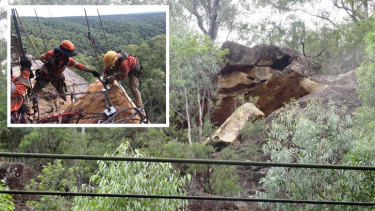 Specialist crews work to secure the boulder above the rail line at Glenbrook.