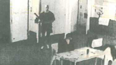 Prison CCTV footage released after Matthew Johnson's court case shows the convicted killer (left) sneaking up behind Carl Williams (seated) with the stem of an exercise bike before launching his deadly attack.