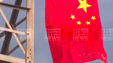 A Swastika symbol and two Chinese flags with COVID-19 written in black on them have been flown on a phone tower north of Melbourne.
