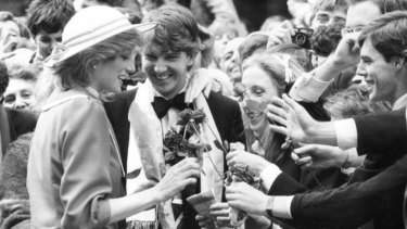 Members of the Trinity College Royalist Society [University of Melbourne] meet Princess Diana and present her with long stemmed roses at the opening of the Bourke Street Mall.