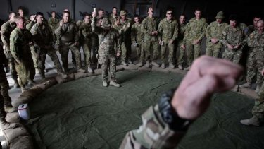 Soldiers play two-up after the ANZAC day dawn service at Multinational Base Tarin Kot, in Afghanistan, on 25 April 2013.