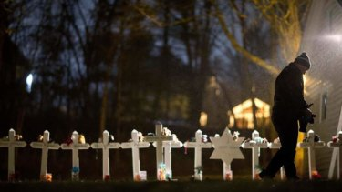 Frank Kulick, walks past a display of wooden crosses, and a Jewish Star of David, representing the victims of the Sandy Hook Elementary School shooting.