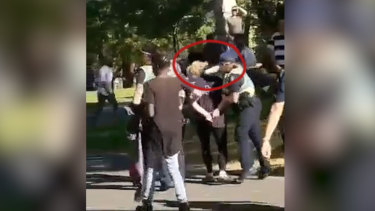 Footage has emerged of a police officer appearing to strike a 15-year-old girl in the head after being spat on.