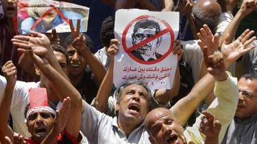 Egyptian protesters shout anti-Muslim Brotherhood slogans as they hold a poster depicting then-president Mohammed Morsi during a protest in Tahrir Square, Cairo, the focal point of the uprising in June 2013.