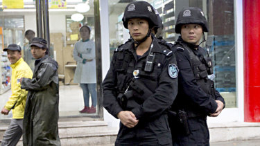 People walk past armed policemen standing guard near the site of an explosion in Urumqi, northwest China's Xinjiang region.