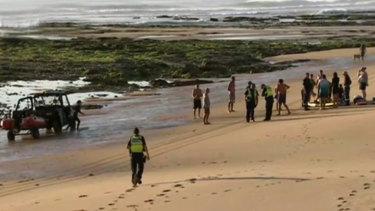 Volunteers bring the two men ashore at Woolamia beach.