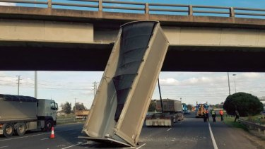 A truck with its trailer raised slammed into a bridge.