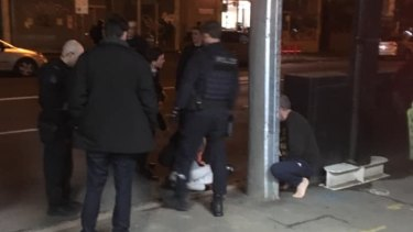 Witness photo shows restrained victim lying on the ground in front of police at Fitzroy on May 11, 2019.