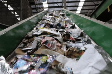 Waste being sorted at a recycling facility. Vision: Planet Art
