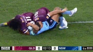 Kaufusi continues the tackle and presses Vaughan's head into the turf.