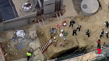 The crane dropped its load of concrete into a pit where three men were working.
