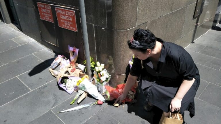 Grace Beyer lays a stone at a floral tribute on Bourke Street.