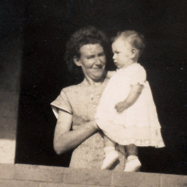 The author's mother, holding toddler Christine, at their completed home.