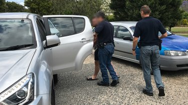 A man is arrested by AFP officers in Caboolture, north of Brisbane, on Tuesday.