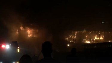 Bystanders watch as fire crews battle flames in the Brisbane primary school classrooms.