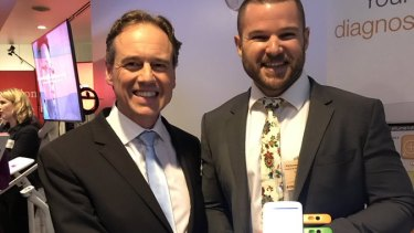 Health Minister Greg Hunt poses with Jim Darrouzet and an Ellume self-testing kit in September 2017.