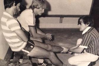 Former Parramatta Eels doctor Peter Manollaras treats Steve Ella as teammate Paul Taylor looks on.