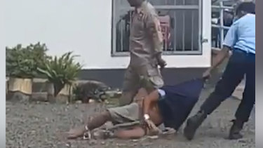 A prisoner is dragged across the gravel in a still from the video.