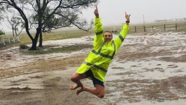 Annabel Hatch jumps for joy in soggy surrounds on her family property in the central Queensland town of Ilfracombe.