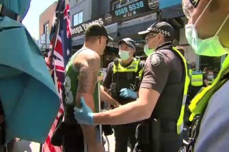 Anti-lockdown protestors and police face off at Eaton Mall in Oakleigh on Monday.