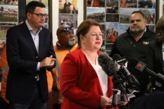 Premier Daniel Andrews in the background, former Essendon great andRawRecruitmentdirector Michael Long (in theRawjacket) and then-Aboriginalaffairs minister Natalie Hutchins at the lectern.