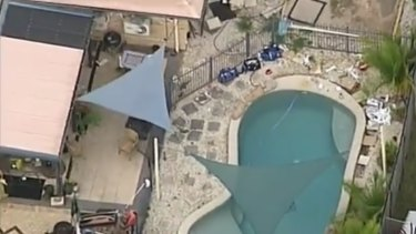The pool in Morayfield where the baby and toddler nearly drowned on Monday. Paramedic equipment sits beside the water.
