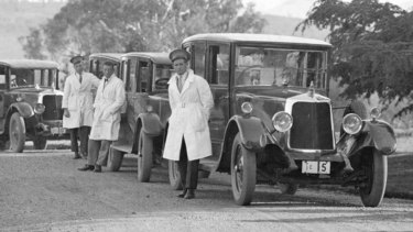 White-coated Commonwealth drivers and their Armstrong Siddeley cars gather at the Governor-General's residence in Yarralumla, circa 1930.