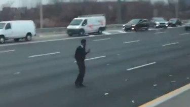 A man picks up dollar notes that spilled on a New Jersey highway.