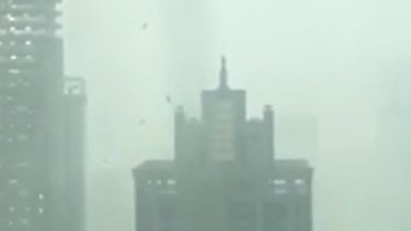 Debris flies off Brisbane high-rise as severe storms hit south-east