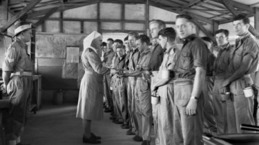 Troops undergoing treatment, line up for Atebrin parade inside mosquito proof ward, 1945.