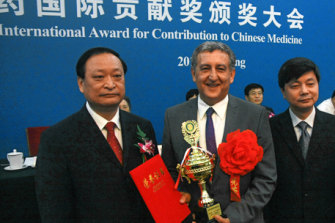 Professor Alan Bensoussan receives the International Award for Contribution to Chinese Medicine at Beijing's Great Hall of the People in 2013, flanked by Chinese Vice-Minister of Health Wang Guoqiang (left).