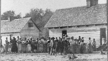 Large group of slaves standing in front of buildings on Smith's Plantation, Beaufort, South Carolina.