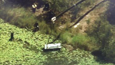 A crane was used to lift the metal toolbox containing the two bodies from a dam at Logan.