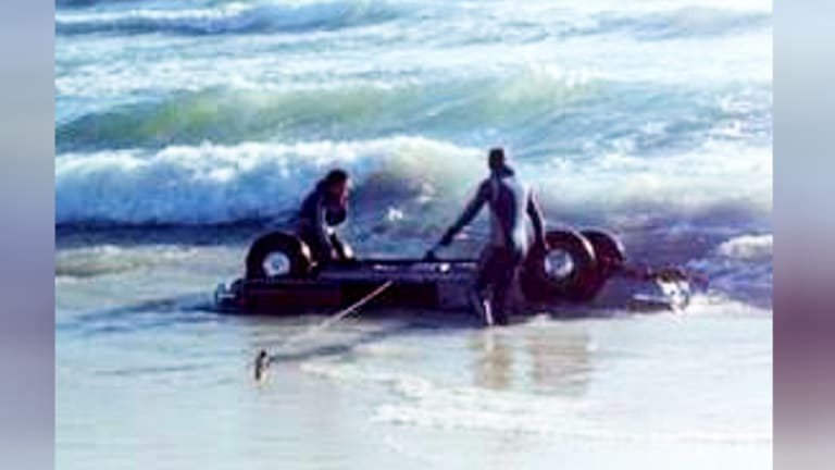 Ms Cutler's car is taken out of the water by two police divers.
