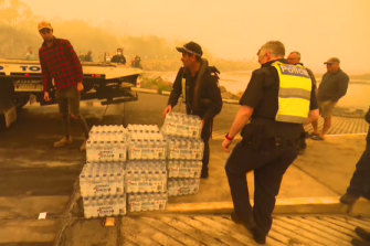 Bottles of water are unloaded at Mallacoota on Thursday.
