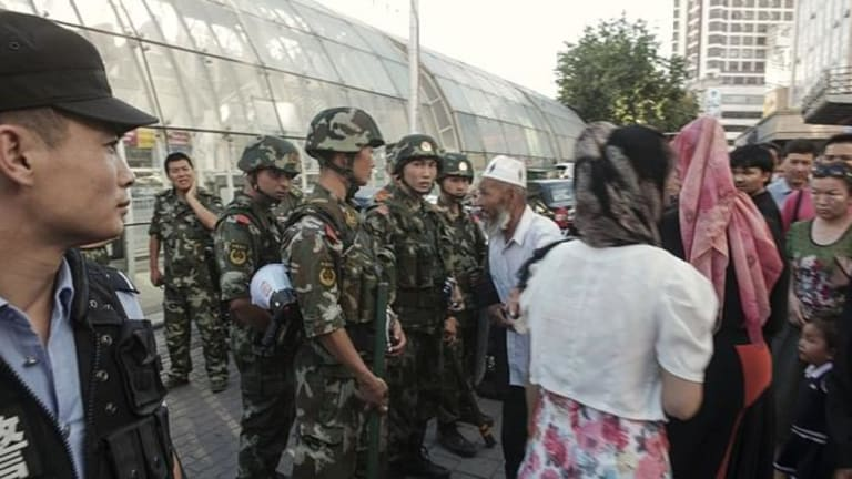 Police stand guard in a Uighur neighbourhood in the Xinjiang region.