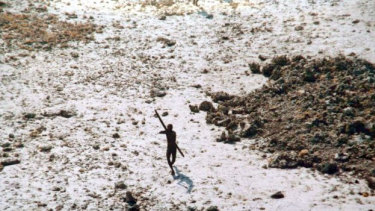 A file photo of a lone Sentinelese tribesman aiming his bow at an Indian coast guard helicopter.