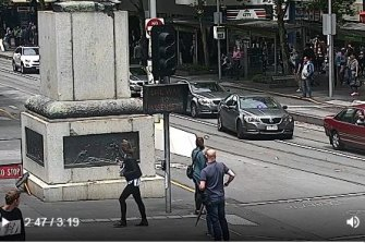 The offender on Swanston Street with police a metre behind him.